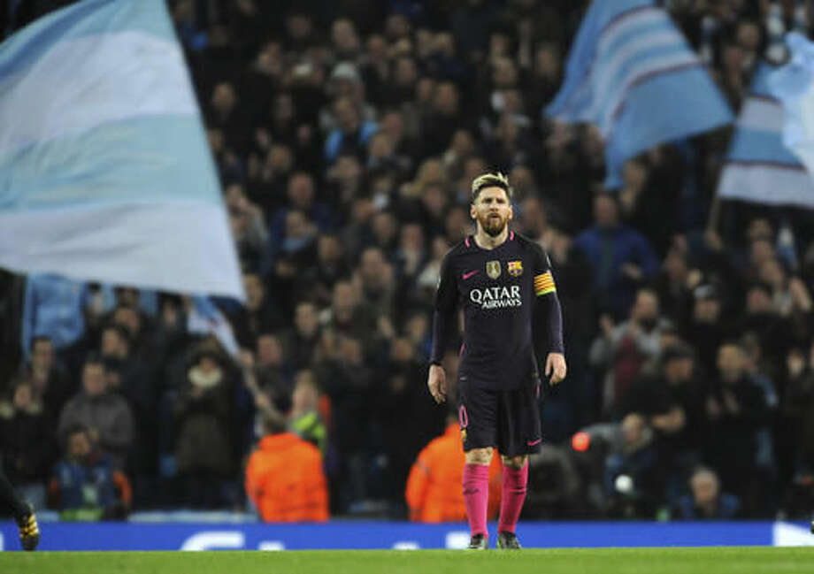 City's supporters wave flags as Barcelona's Lionel Messi stands on the pitch after the Champions League group C soccer match between Manchester City and Barcelona at the Etihad stadium in Manchester, England, Tuesday, Nov. 1, 2016. Manchester City defeated Barcelona by 3-1. (AP Photo/Rui Vieira)
