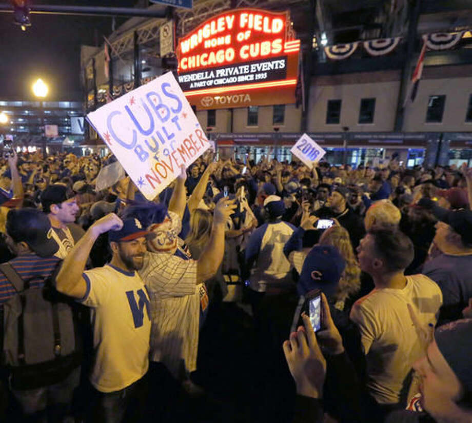 Chicago Cubs fans celebrate outside Wrigley Field in Chicago, after the Cubs' 9-3 win over the Cleveland Indians in Cleveland in Game 6 of the baseball World Series, Tuesday, Nov. 1, 2016. The Cubs are scheduled to face the Indians in the decisive Game 7 Wednesday. (AP Photo/Charles Rex Arbogast)