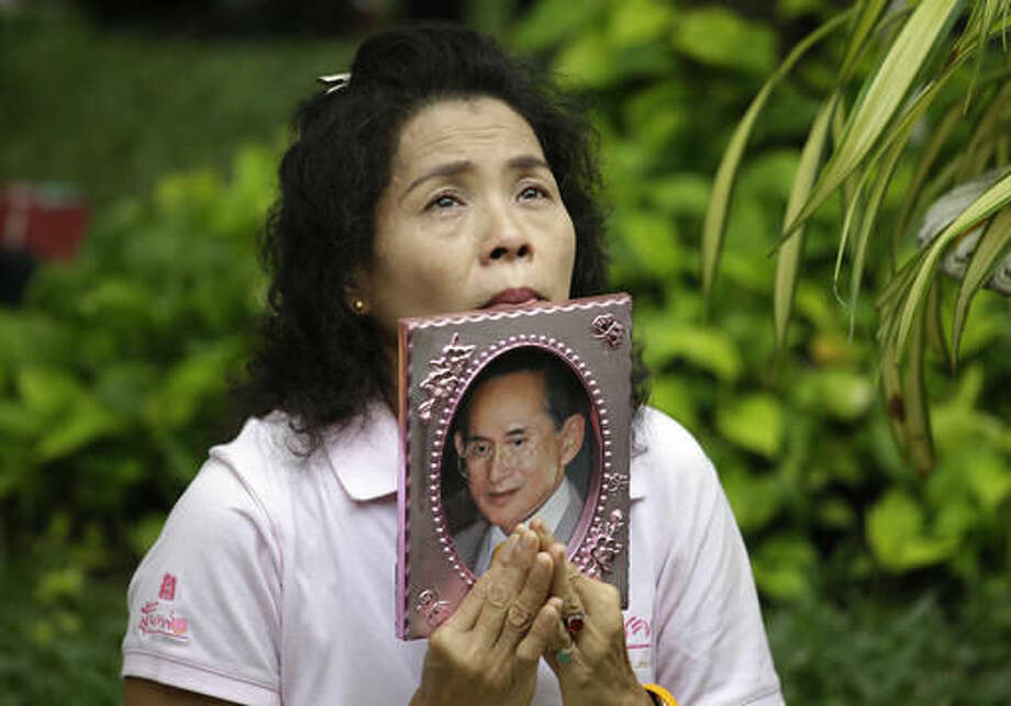 A Thai woman holds a portrait of Thai King Bhumibol Adulyadej while praying at Siriraj Hospital where the king is being treated, in Bangkok, Thailand, Thursday, Oct. 13, 2016. The royal palace said in a statement late Wednesday that the 88-year-old king's blood pressure had dropped, his liver and kidneys were not working properly and he remained on a ventilator. (AP Photo/Sakchai Lalit)