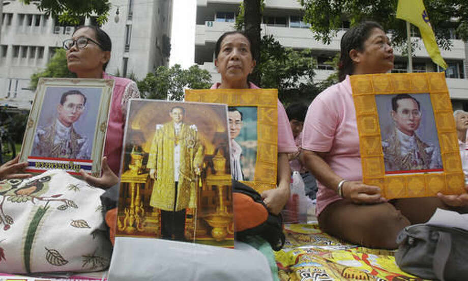Thais hold portraits of Thai King Bhumibol Adulyadej at Siriraj Hospital where the king is being treated in Bangkok, Thailand, Thursday, Oct. 13, 2016. The royal palace said in a statement late Wednesday that the 88-year-old king's blood pressure had dropped, his liver and kidneys were not working properly and he remained on a ventilator. (AP Photo/Sakchai Lalit)