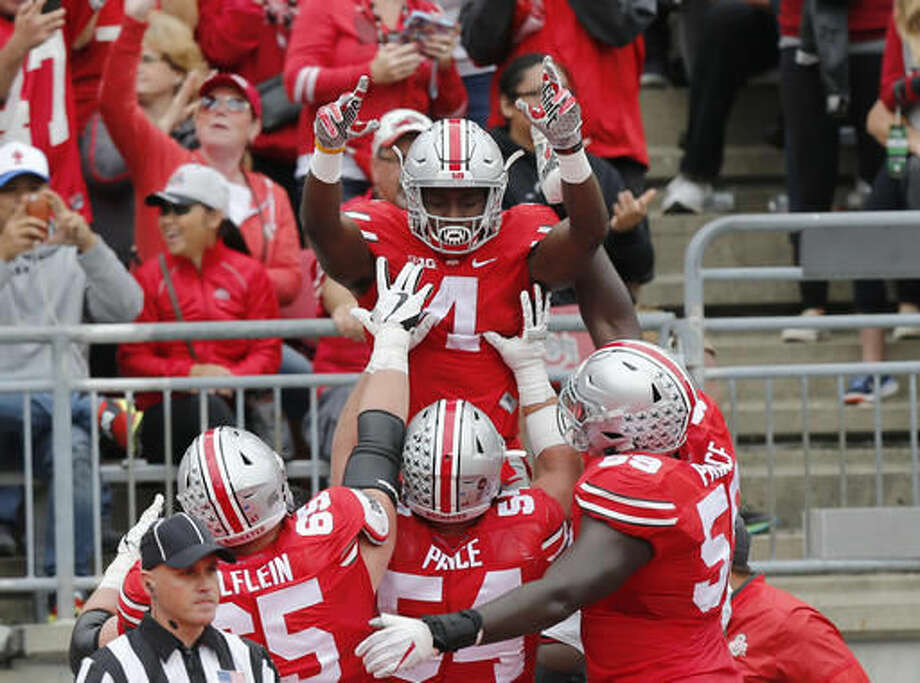 FILE - In this Oct. 1, 2016, file photo, Ohio State running back Curtis Samuel, top, celebrates his touchdown against Rutgers during the first half of an NCAA college football game in Columbus, Ohio. With the help of a loving family that kept his priorities straight and a well-connected high school coach, Samuel went from hearing the rumble of the elevated subway train next to Sid Luckman Field to the roar of 100,000 Ohio State fans at the Horseshoe. (AP Photo/Jay LaPrete, File)