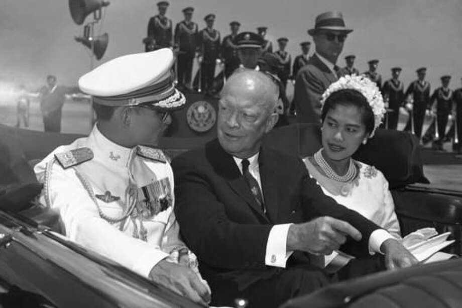 FILE - In this June 28, 1960, file photo, U.S. President Dwight Eisenhower, center, is seated between Thailand's King Bhumibol Adulyadej, left, and Queen Sirikit for a motorcade drive from National Airport to the White House in Washington. Thailand's Royal Palace said on Thursday, Oct. 13, 2016, that Thailand's King Bhumibol Adulyadej, the world's longest-reigning monarch, has died at age 88. (AP Photo, File)