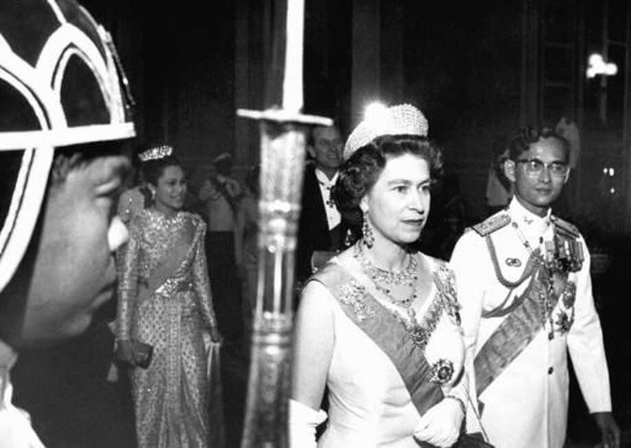 FILE - In this Feb. 11, 1972, file photo, Britain's Queen Elizabeth II walks with Thailand's King Bhumibol Adulyadej, right, with Queen Sirikit at rear left and Prince Philip at rear right, in Bangkok. Thailand's Royal Palace said on Thursday, Oct. 13, 2016, that Thailand's King Bhumibol Adulyadej, the world's longest-reigning monarch, has died at age 88. (AP Photo, File)