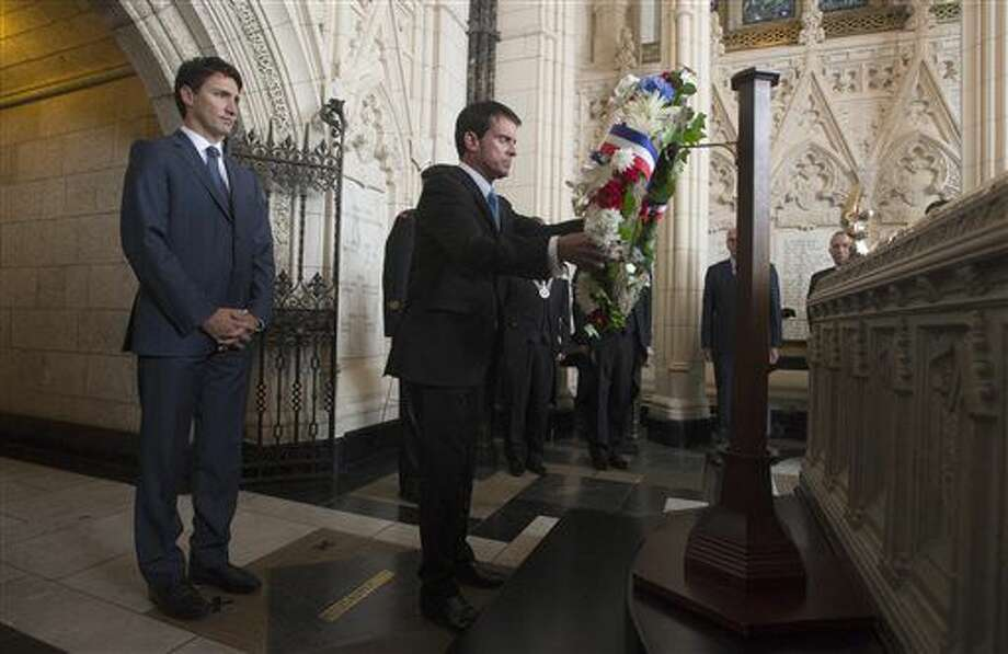 Canadian Prime Minister Justin Trudeau looks on as French Prime Minister Manuel Valls places a wreath in the Memorial Chapel on Parliament Hill in Ottawa, Thursday Oct.13, 2016. (Adrian Wyld/The Canadian Press via AP)