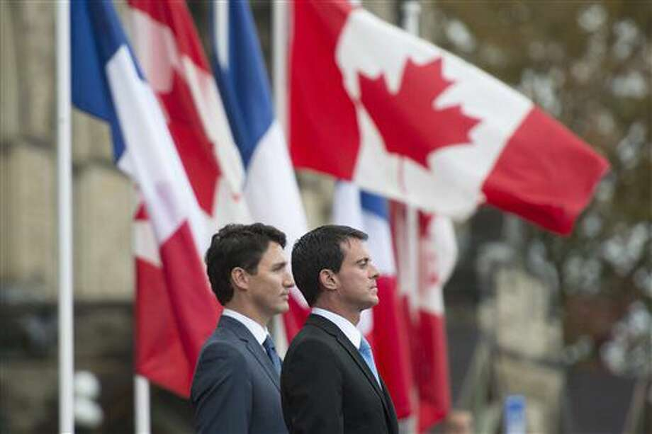 Canadian Prime Minister Justin Trudeau stands beside French Prime Minister Manuel Valls as he is welcomed on Parliament Hill in Ottawa, Thursday Oct.13, 2016. (Adrian Wyld/The Canadian Press via AP)
