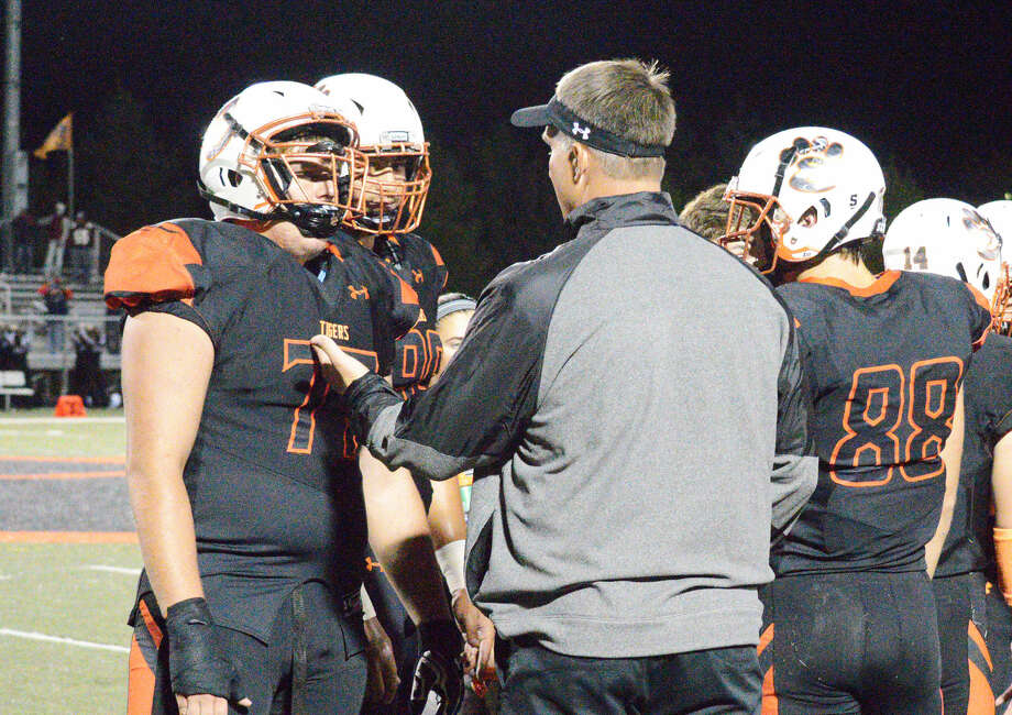 Edwardsville coach Matt Martin, right, talks to his defensive linemen Tate Rujawitz, left, and AJ Epenesa last week.