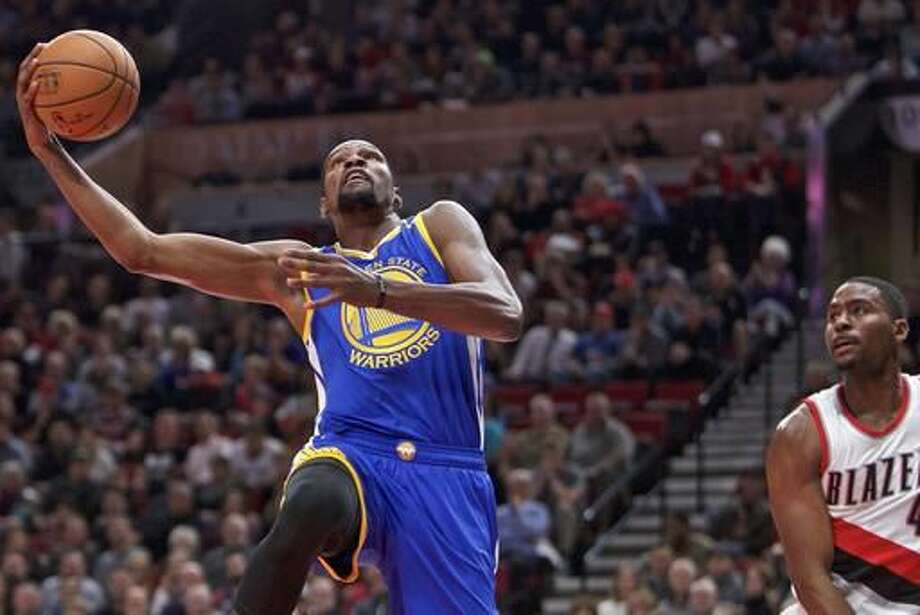 Golden State Warriors forward Kevin Durant, left, dunks past Portland Trail Blazers forward Maurice Harkless, right, during the first half of an NBA basketball game in Portland, Ore., Tuesday, Nov. 1, 2016. (AP Photo/Craig Mitchelldyer)