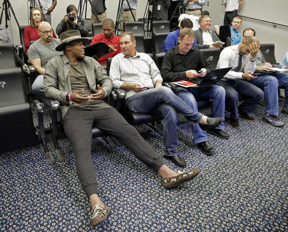 Carolina Panthers' Cam Newton, left, talks to the media before a news conference in Charlotte, N.C., Wednesday, Nov. 2, 2016. Newton spoke briefly about meeting with NFL commissioner Roger Goodell after complaining that he didn't feel officials were protecting him in the pocket. (AP Photo/Chuck Burton)