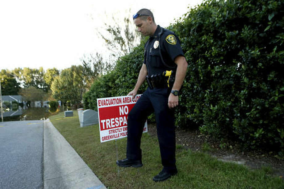 Lt. Mike Broadwell of the Greenville Police Department installs a No Trespassing sign near a neighborhood flooded by water associated with Hurricane Matthew, Wednesday, Oct. 12, 2016, in Greenville, N.C. (AP Photo/Brian Blanco)