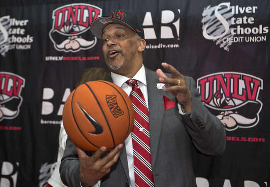 FILE - In this April 22, 2016, file photo, new UNLV men's basketball coach Marvin Menzies poses before the media and invited guests sporting a new hat and ball in Las Vegas, after the UNLV board of regents approved his contract. Menzies had to scramble to fill his roster after behind hired at UNLV and injuries have hit the Runnin' Rebels hard in the preseason. Needless to say, it could take a little while for the Rebels to gel. (L.E. Baskow/Las Vegas Sun via AP, File)