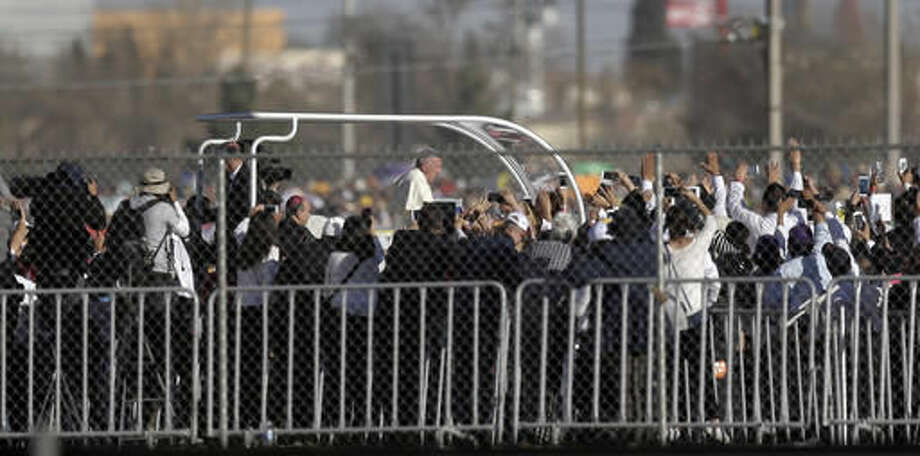 FILE - In this Feb. 17, 2016 file photo, Pope Francis is seen through U.S. border fence in El Paso, Texas, along the banks of the Rio Grande as he arrives in Juarez, Mexico. The pope, in his annual message for the World Day of Migrants and Refugees on Thursday, Oct. 13, 2016, denounced the forced repatriation of unaccompanied children migrants who flee wars and poverty, saying countries should try to meet their needs rather than return them to uncertain futures back home. (AP Photo/Eric Gay, File)