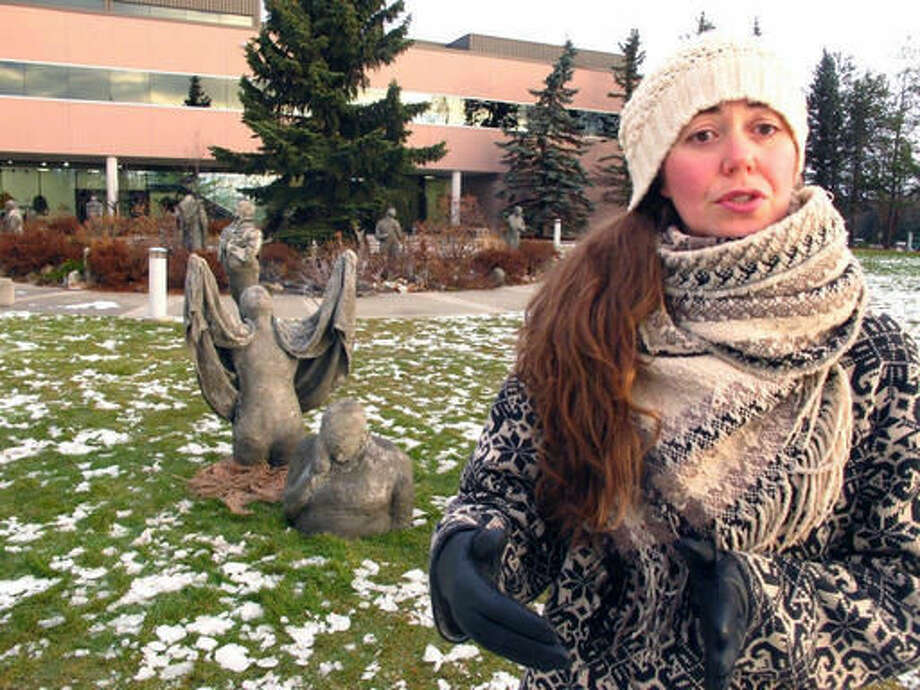 Artist Sarah Davies stands near statues in a new public art installation Wednesday, Nov. 2, 2016, at Alaska Pacific University in Anchorage, Alaska. Davies was also the lead artist in an art installation that included the sculptures, which have been restored for the exhibit opening Friday after they were damaged by tides and high winds last year. (AP Photo/Rachel D'Oro)