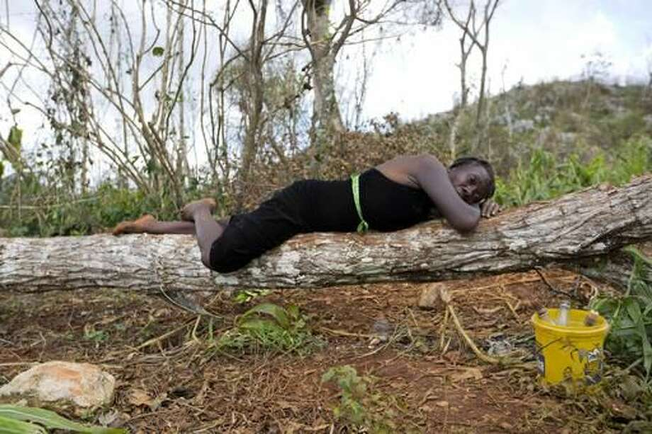 Bernadette Simeon lies on a downed tree as she sells gasoline along the road after Hurricane Matthew affected Beaumont, a district of Jeremie, Haiti, Wednesday, Oct. 12, 2016. Simeon, 41, said she lost everything to the hurricane, and lamented that her kids couldn't go to school because the buildings were destroyed and they lost books and uniforms. (AP Photo/Dieu Nalio Chery)