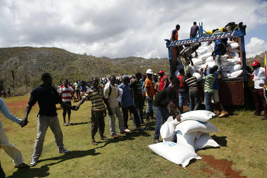Sacks of donated rice are loaded onto a truck for local distribution after being delivered by a U.S. military helicopter, in the mountain village of Beaumont, near Jeremie, Haiti, Thursday, Oct. 13, 2016. An international relief effort for victims of Hurricane Matthew entered a more advanced stage Thursday as a second U.S. military ship arrived off Haiti's coast and U.N. convoys and non-government organizations began reaching more isolated communities. (AP Photo/Rebecca Blackwell)