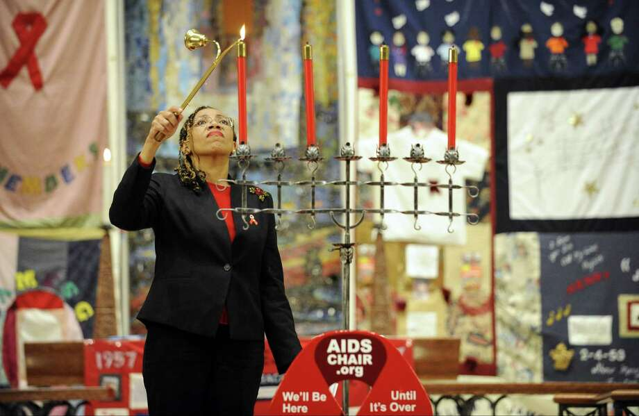 Dr. Jennifer Clader, Director of Health, City of Stamfod, lights the first of four candles during the 19th Annual World AIDS Day commemoration interfaith service at First United Methodist Church in Stamford on Dec. 1, 2016. In conjunction with World AIDS Day 2016, 15 clergy gathered to lead a service of Remembrance, Awareness, Hope and Healing for people whose lives have been touched by HIV/AIDS.  The service, sponsored by AIDS Interfaith Stamford, brings together Protestant, Catholic, Islamic and Jewish clergy in a service designed to remember those who have died, and to offer hope and healing to people living with AIDS and HIV infection and those who love and care for them. Photo: Matthew Brown / Hearst Connecticut Media / Stamford Advocate