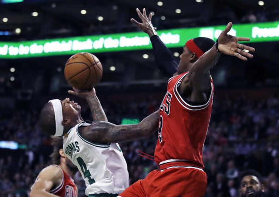 Chicago Bulls guard Rajon Rondo, right, blocks a shot by Boston Celtics guard Isaiah Thomas (4) during the first quarter of an NBA basketball game in Boston, Wednesday, Nov. 2, 2016. (AP Photo/Charles Krupa)