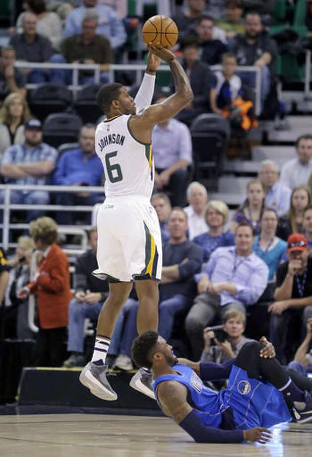 Utah Jazz forward Joe Johnson (6) shoots as Dallas Mavericks guard Wesley Matthews falls during the first quarter of an NBA basketball game Wednesday, Nov. 2, 2016, in Salt Lake City. (AP Photo/Rick Bowmer)
