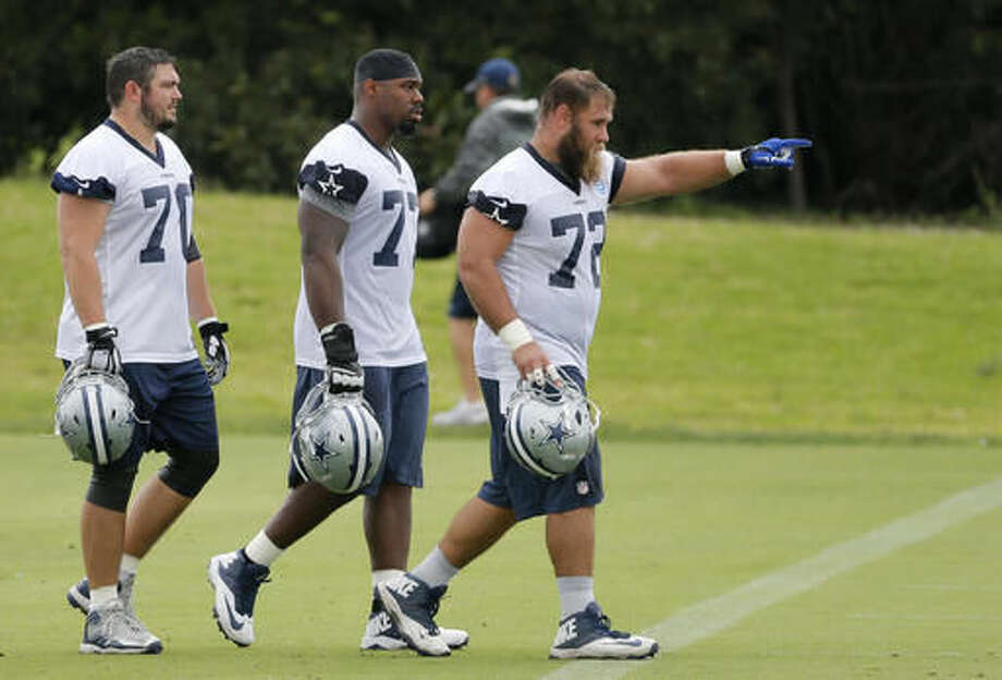 FILE - In this June 1, 2016, file photo, Dallas Cowboys' Zack Martin (70), Tyron Smith, center, and Travis Frederick, right, walk across the field as they participate in a workout during an NFL football training camp in Irving, Texas. Smith and Frederick signed lucrative second contracts with Dallas after starting right away as first-round picks, and Martin is next.(AP Photo/Tony Gutierrez, File)