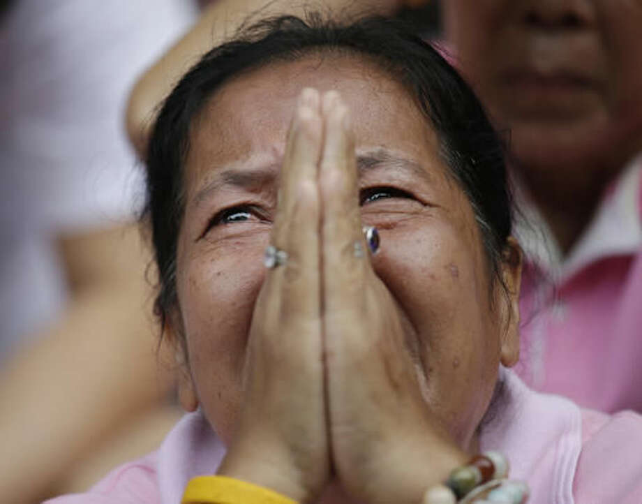 A woman prays for Thailand's King Bhumibol Adulyadej outside Siriraj Hospital where the king is being treated in Bangkok, Thailand, Thursday, Oct. 13, 2016. The royal palace said in a statement late Wednesday that the 88-year-old king's blood pressure had dropped, his liver and kidneys were not working properly and he remained on a ventilator. (AP Photo/Sakchai Lalit)