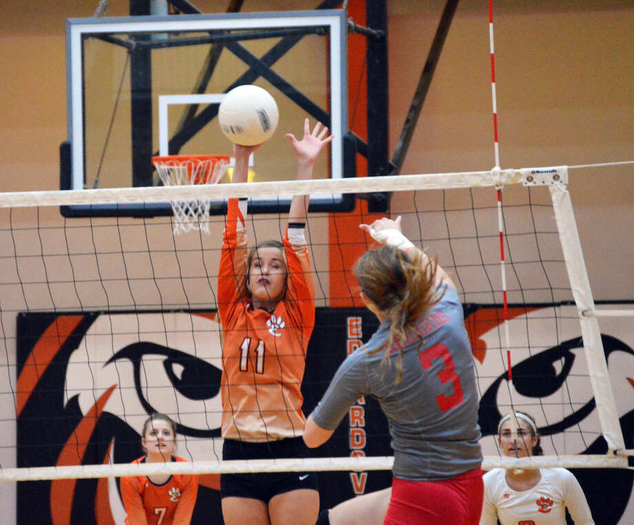Edwardsville's Shelbey Saye gets her right hand on a kill attempt by an Alton hitter at the net during first-game action at Lucco-Jackson Gymnasium.