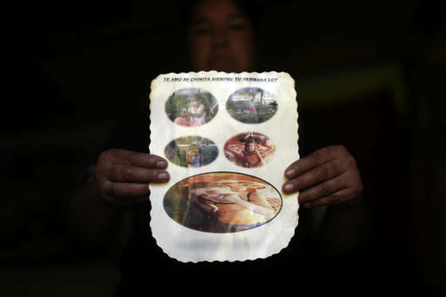 In this 22 Oct. 2016 photo, Juana Poblete, poses with photos of her daughter, Lissette who died under the care of the Chilean state, in Til Til, Chile. Lissette's case exploded in a crisis over the care of at-risk children that has outraged Chileans. After initially reporting just 185 deaths, the government recently acknowledged that 865 children have died under the care of the National Service for Minors over 11 years. (AP Photo/Luis Hidalgo).
