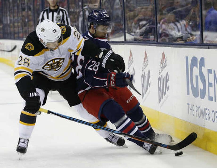 Boston Bruins' John-Michael Liles, left, and Columbus Blue Jackets' Oliver Bjorkstrand vie for a loose puck during the second period of an NHL hockey game Thursday, Oct. 13, 2016, in Columbus, Ohio. (AP Photo/Jay LaPrete)