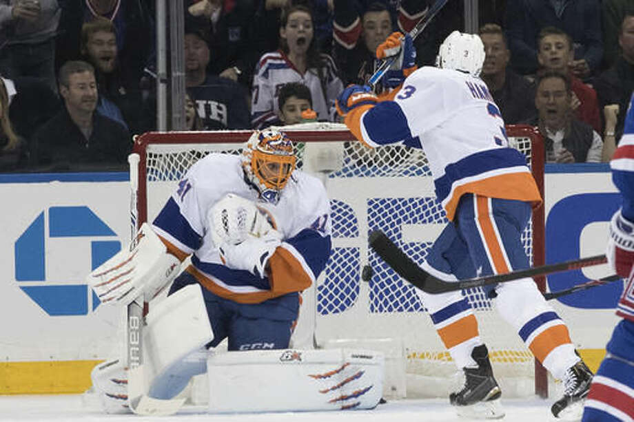 New York Islanders goalie Jaroslav Halak (41) and defenseman Travis Hamonic (3) watch as the puck hits the net after New York Rangers right wing Michael Grabner scored a goal during the first period of an NHL hockey game, Thursday, Oct. 13, 2016, at Madison Square Garden in New York. (AP Photo/Mary Altaffer)