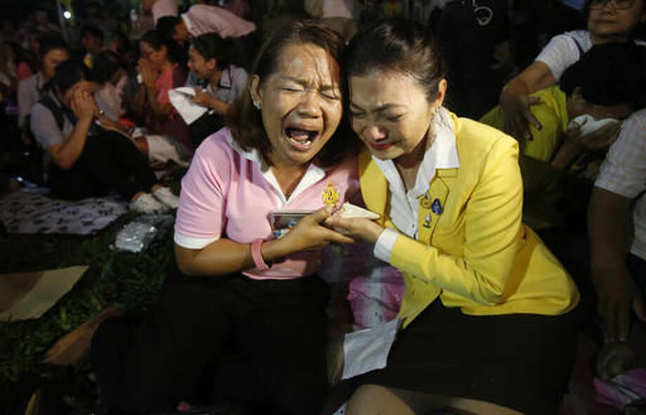 Thai cry at Siriraj Hospital where the king is being treated in Bangkok, Thailand, Thursday, Oct. 13, 2016. Thailand's Royal Palace said King Bhumibol Adulyadej, the world's longest-reigning monarch, has died at age 88. (AP Photo/Sakchai Lalit)