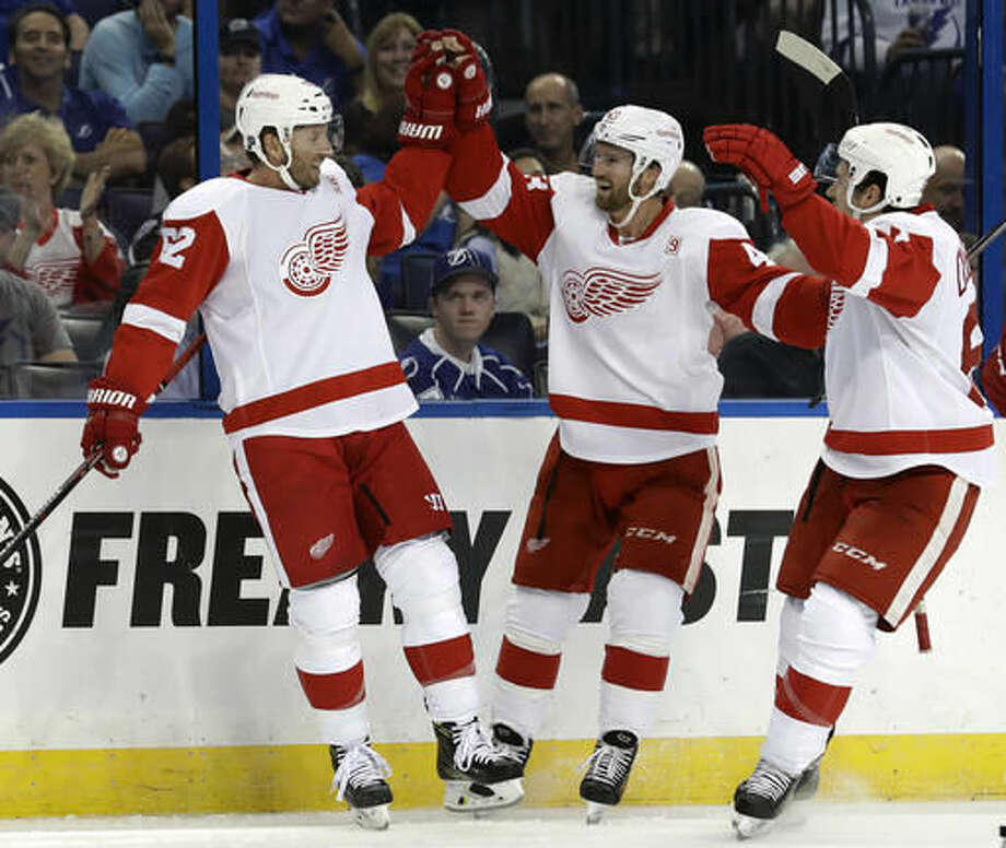 Detroit Red Wings left wing Thomas Vanek, left, of Austria, celebrates his goal against the Tampa Bay Lightning with teammates Darren Helm, center, and Xavier Ouellet during the first period of an NHL hockey game Thursday, Oct. 13, 2016, in Tampa, Fla. (AP Photo/Chris O'Meara)
