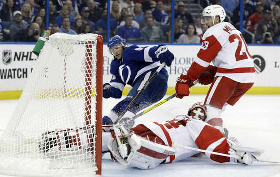 Detroit Red Wings goalie Petr Mrazek (34), of the Czech Republic, robs Tampa Bay Lightning center Steven Stamkos (91) during the second period of an NHL hockey game Thursday, Oct. 13, 2016, in Tampa, Fla. Red Wings' Drew Miller (20) teails the play. (AP Photo/Chris O'Meara)