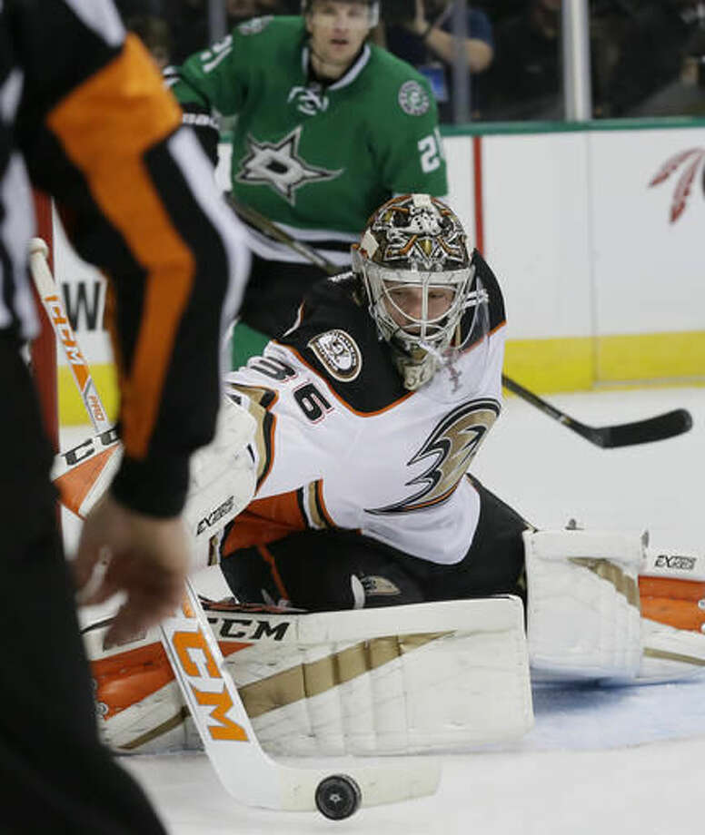 Anaheim Ducks goalie John Gibson (36) deflects a shot as Dallas Stars left wing Antoine Roussel (21) looks on during the first period of an NHL hockey game Thursday, Oct. 13, 2016, in Dallas. (AP Photo/LM Otero)