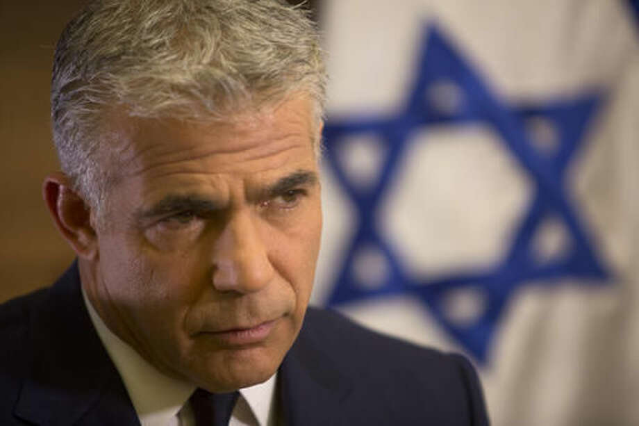 In this Monday, Oct. 31, 2016 photo, Israeli Knesset member, Yair Lapid, leader of the Yesh Atid party, gives an interview to The Associated Press, in his office at the Knesset, Israel's parliament, in Jerusalem. Lapid believes he has finally found a formula that will allow him to do something that has eluded Israeli politicians for nearly a decade: Defeat Prime Minister Benjamin Netanyahu in an election. Just three years after Lapid gave up a successful media career for the rough-and-tumble of Israeli politics, his centrist Yesh Atid party has been surging in opinion polls -- repeatedly coming out ahead of Netanyahu's long-dominant Likud Party. (AP Photo/Sebastian Scheiner)