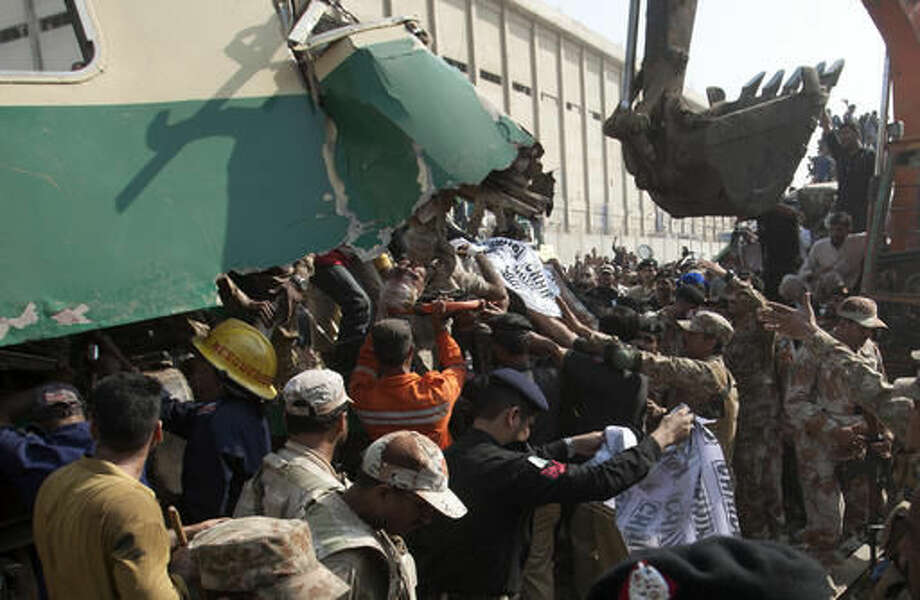 People remove an injured passenger from a wreckage of a train collided with another train in Karachi, Pakistan, Thursday, Nov. 3, 2016. Pakistani officials say a train crash has killed dozens of people in the southern port city. (AP Photo/Shakil Adil)