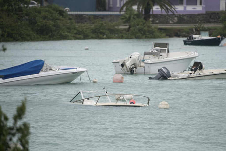 Swamped boats sit in Mullet Bay after the passing of Hurricane Nicole in St. Georges, Bermuda, Thursday, Oct. 13, 2016. Hurricane Nicole roared across Bermuda, pummeling the resort island with winds up to 115 mph that snapped trees and peeled off roofs before the storm spun away into open water. (AP Photo/Mark Tatem)
