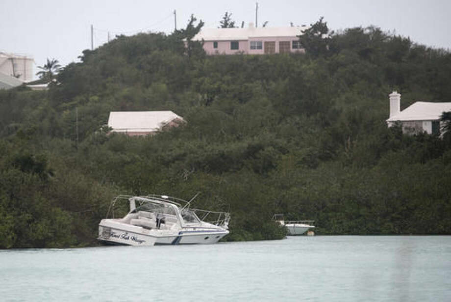A boat that broke from its moorings lays ashore at Ferry Reach, St. Georges, Bermuda, Thursday, Oct. 13, 2016. Hurricane Nicole roared across Bermuda, pummeling the resort island with winds up to 115 mph that snapped trees and peeled off roofs before the storm spun away into open water. (AP Photo/Mark Tatem)