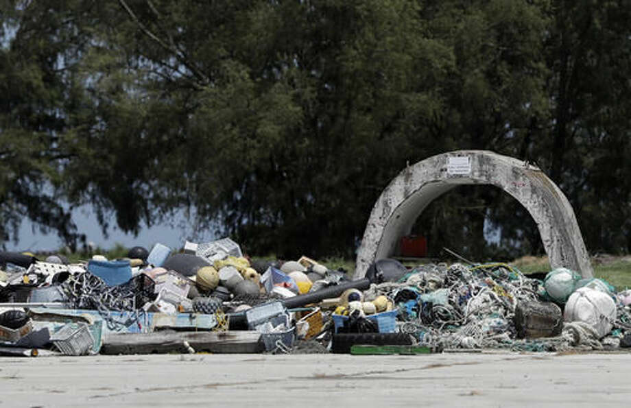 FILE - In this Sept. 1, 2016 file photo, plastic and other marine debris is piled on Midway Atoll in the Papahanaumokuakea Marine National Monument, Northwestern Hawaiian Islands, during a tour by President Barack Obama. The Battle of Midway was a major turning point in World War II's Pacific theater. But the remote atoll where thousands died is now a delicate sanctuary for millions of seabirds, and a new battle is pitting preservation of its vaunted military history against the protection of its wildlife. Midway is on the edge of a recently expanded marine national monument. (AP Photo/Carolyn Kaster, File)