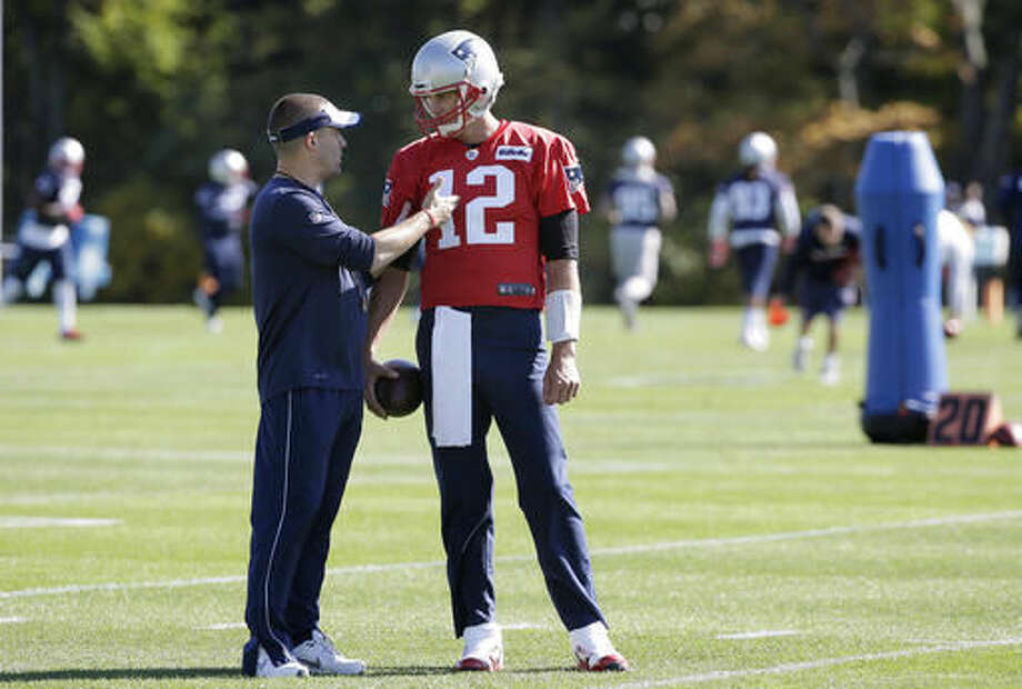New England Patriots offensive coordinator Josh McDaniels, left, speaks with quarterback Tom Brady, right, during an NFL football practice Wednesday, Oct. 12, 2016, in Foxborough, Mass. (AP Photo/Steven Senne)