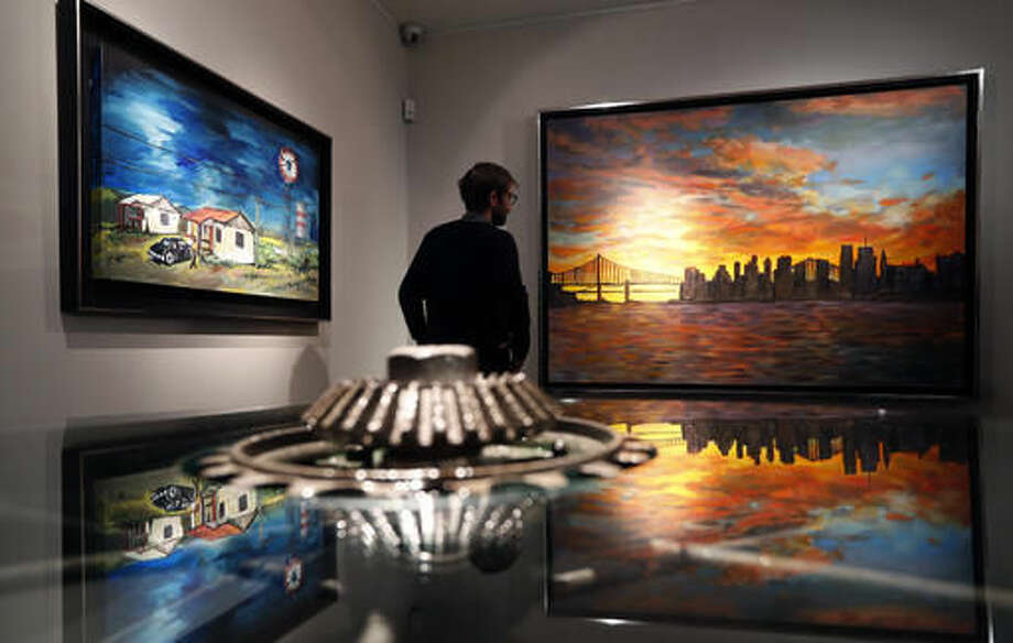 "A man looks towards a painting by Bob Dylan called ""New York Skyline, seen from Queens,"" right, and ""Threatening Skies,"" left, reflected in an artwork called ""Ironwork Table"" at an exhibition called Bob Dylan The Beaten Path, at the Halcyon Gallery in London, Tuesday, Nov. 1, 2016. The exhibition opens on Nov. 5 and runs until Dec. 11. (AP Photo/Kirsty Wigglesworth)"