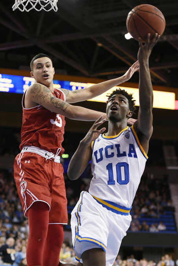 FILE - In this Feb. 18, 2016, file photo, UCLA guard Isaac Hamilton shoots as Utah forward Kyle Kuzma defends during an NCAA college basketball game in Los Angeles. The preseason Top 25 that was released Monday includes five teams that failed to reach the 2016 NCAA Tournament. UCLA is ranked 16th despite finishing below .500 last season. The Bruins return four starters from last season. (AP Photo/Kelvin Kuo, File)