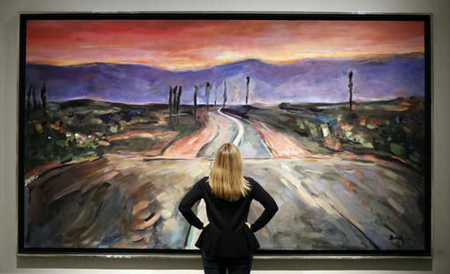 "A woman looks towards a painting by Bob Dylan called ""Endless Highway"" on display at the exhibition called Bob Dylan The Beaten Path, at the Halcyon Gallery in London, Tuesday, Nov. 1, 2016. The exhibition opens on Nov. 5 and runs until Dec. 11. (AP Photo/Kirsty Wigglesworth)"