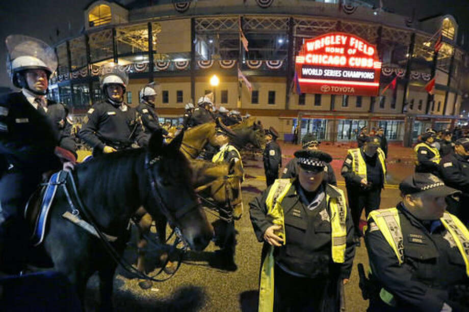 Members of Chicago's Mounted Police unit along with others maintain their post outside Wrigley Field in Chicago on Thursday, Nov. 3, 2016, after the Cubs beat the Cleveland Indians 8-7 in Game 7 of the Major League World Series in Cleveland. (AP Photo/Charles Rex Arbogast)