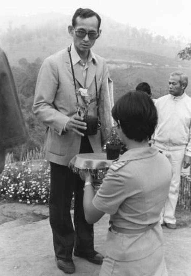 FILE - In this Feb. 16, 1981, file photo, Thai King Bhumibol Adulyadej receives a small plant from a Thai woman as he makes a visit to one of his crop substitution projects in Northern Thailand. The king's time in the countryside probably did much to shape his idealized vision of Thailand, one more rooted in a self-sufficient agricultural society than urban aspirations and values that were taking hold. (AP Photo/Jeff Robbins, File)