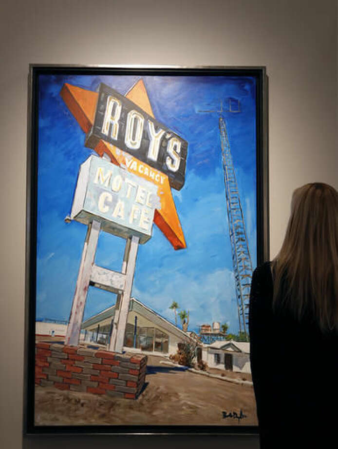 "A woman looks towards a painting by Bob Dylan called ""Abandoned Motel, Eureka"" at an exhibition called Bob Dylan The Beaten Path, at the Halcyon Gallery in London, Tuesday, Nov. 1, 2016. The exhibition opens on Nov. 5 and runs until Dec. 11. (AP Photo/Kirsty Wigglesworth)"