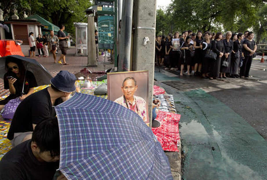 A portrait of Thai King Bhumibol Adulyadej, center is displayed as Thai people stand in lines to offer condolences for the king at Grand Palace in Bangkok, Thailand, Friday, Oct. 14, 2016. Grieving Thais went to work dressed mostly in black Friday morning, just hours after the palace announced the death of their beloved King Bhumibol, the politically fractious country's unifying figure and the world's longest-reigning monarch.(AP Photo/ Gemunu Amarasinghe)