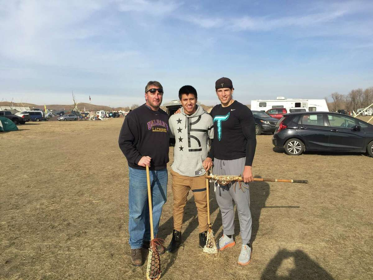 UAlbany men's lacrosse coach Scott Marr, left, his former player Lyle Thompson, center, and Bill O'Brien, both members of the Onondaga Nation, organized a lacrosse game at the Standing Rock Sioux pipeline protest in North Dakota on Nov. 22. (Phot courtesy of Scott Marr)
