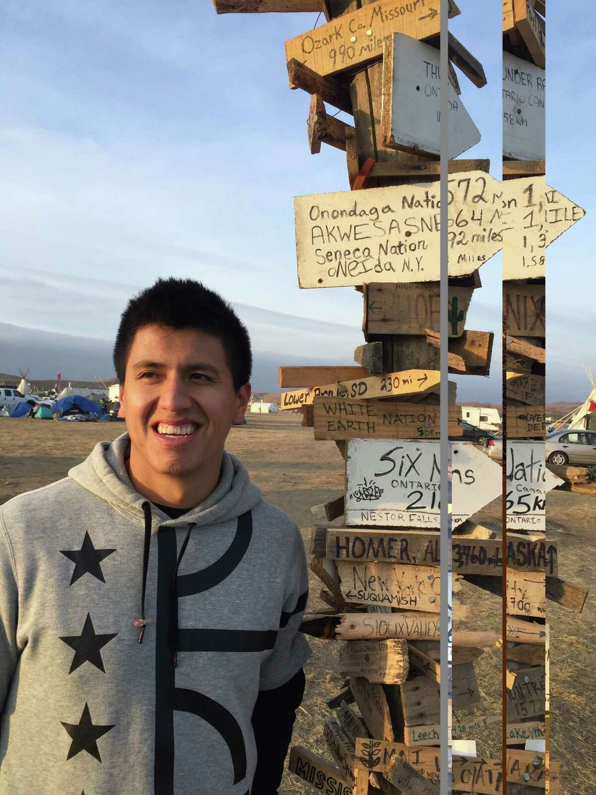 Former UAlbany lacrosse player Lyle Thompson stands in front of a sign showing directions to Native American reservations, including his own, Six Nations in Canada, at the Standing Rock Sioux pipeline protest in Cannon Ball, N.D. (Photo courtesy of Scott Marr)