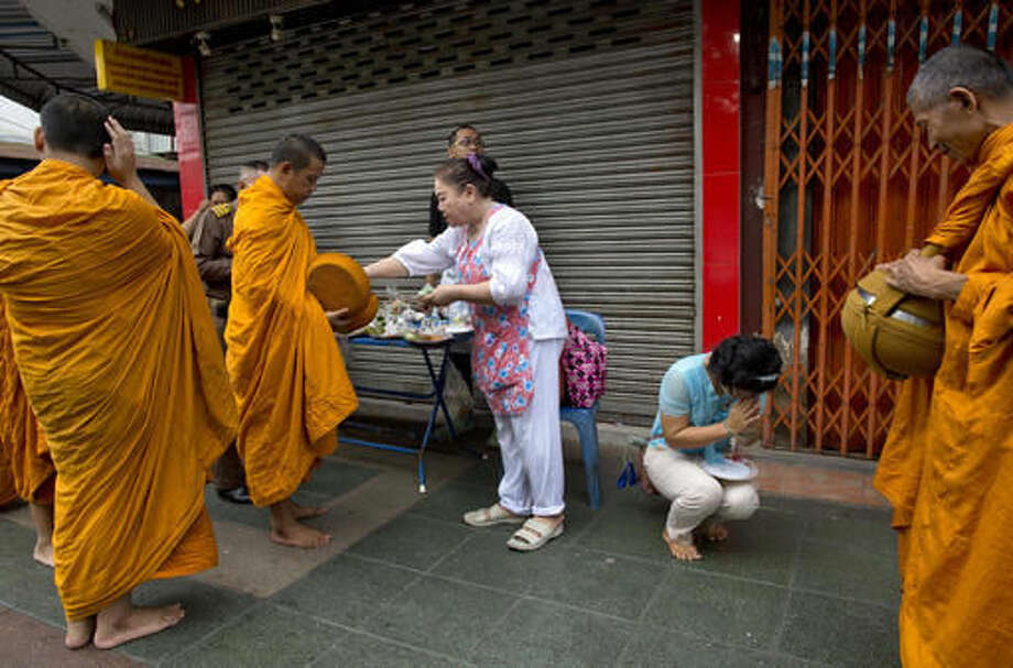 Thai people, some dressed in black, offer alms for Buddhist monks close to Grand Palace in Bangkok, Thailand, Friday, Oct. 14, 2016. Grieving Thais went to work dressed mostly in black Friday morning, just hours after the palace announced the death of their beloved King Bhumibol Adulyadej, the politically fractious country's unifying figure and the world's longest-reigning monarch.(AP Photo/ Gemunu Amarasinghe)