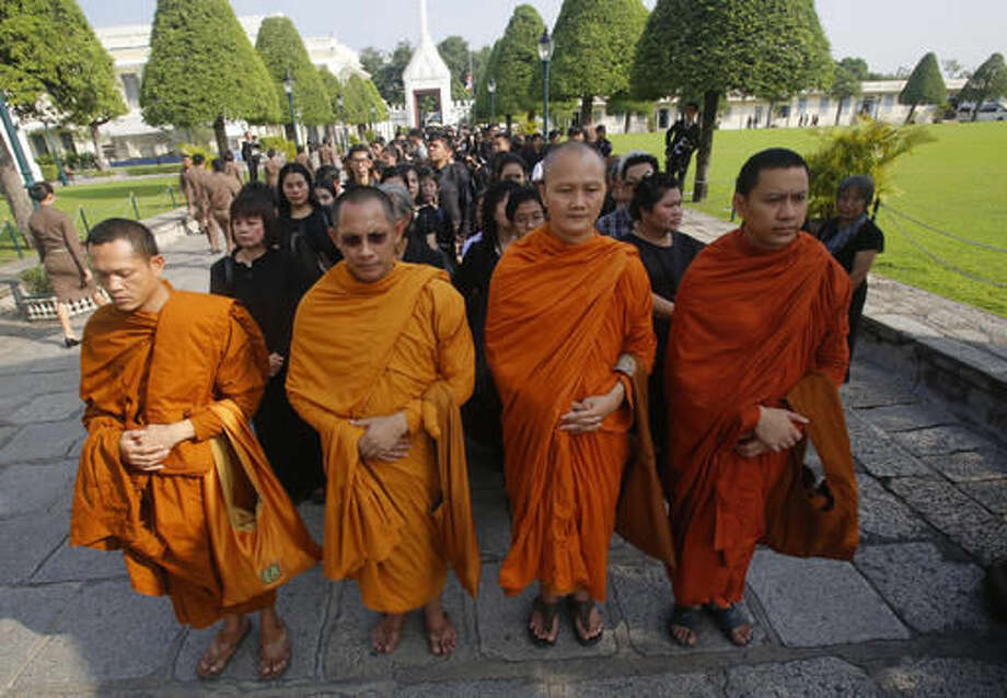 Buddhist monks and Thais line up to offer condolences for Thailand's King Bhumibol Adulyadej at Grand Palace in Bangkok, Thailand, Friday, Oct. 14, 2016. Grieving Thais went to work dressed mostly in black Friday morning, just hours after the palace announced the death of their beloved King Bhumibol, the politically fractious country's unifying figure and the world's longest-reigning monarch. He was 88. (AP Photo/Sakchai Lalit)