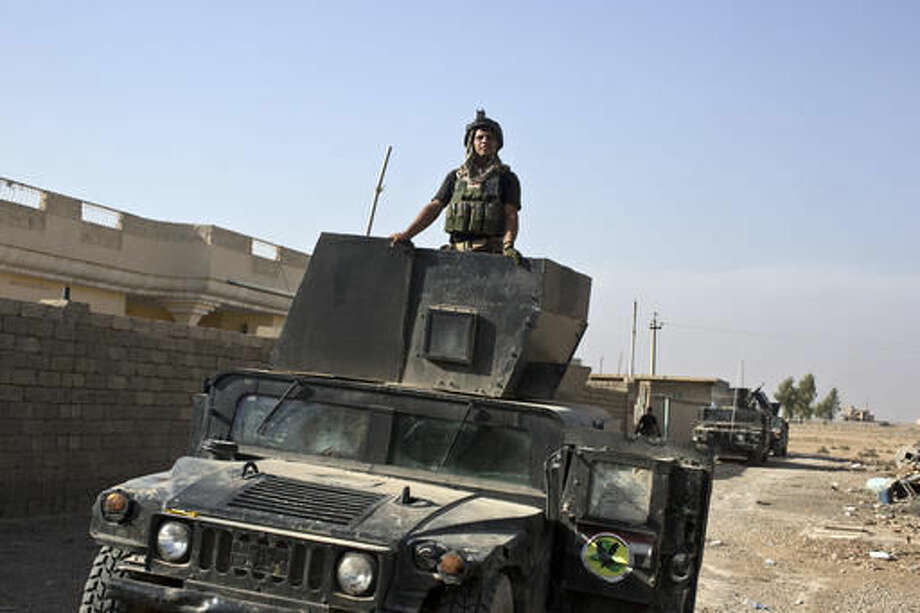 An Iraqi special forces soldier stands atop a Humvee in the village of Bazwaya, some 8 kilometers from the center of Mosul, Iraq, Monday, Oct. 31, 2016. Iraqi special forces stood poised to enter Mosul in an offensive to drive out Islamic State militants after sweeping into the last village on the city's eastern edge Monday while fending off suicide car bombs without losing a soldier. (AP Photo/Marko Drobnjakovic)
