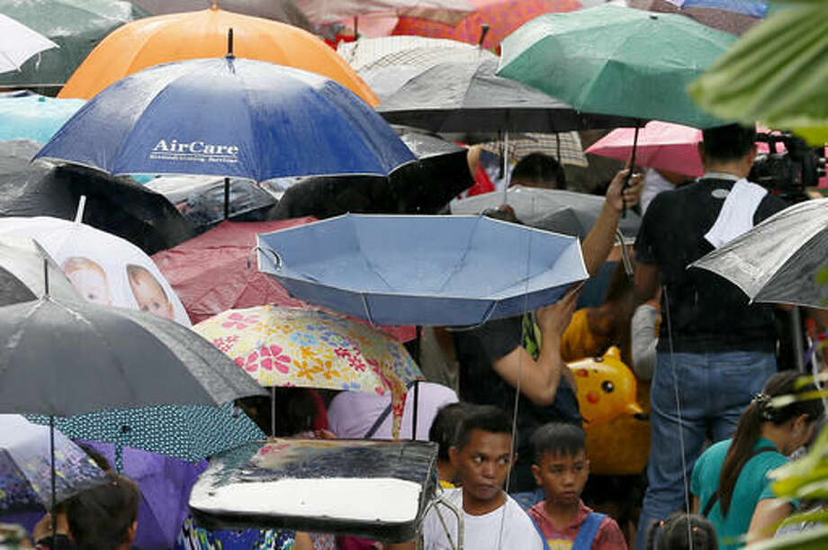 Under a slight rainfall, Filipinos throng to Manila's North Cemetery, the country's largest, to pay tribute to their departed in observance of All Saints Day Tuesday, Nov. 1, 2016 in Manila, Philippines. Tens of thousands of Filipinos in this predominantly Catholic nation in Asia, take their time to visit the graves of their dear departed by offering flowers and prayers in the annual tradition. (AP Photo/Bullit Marquez)